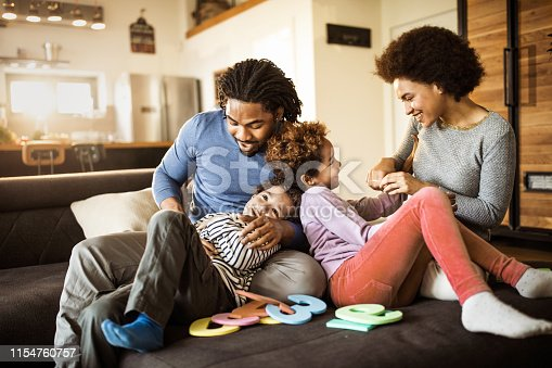 1159543952istockphoto Young happy black parents having fun with their small kids at home. 1154760757