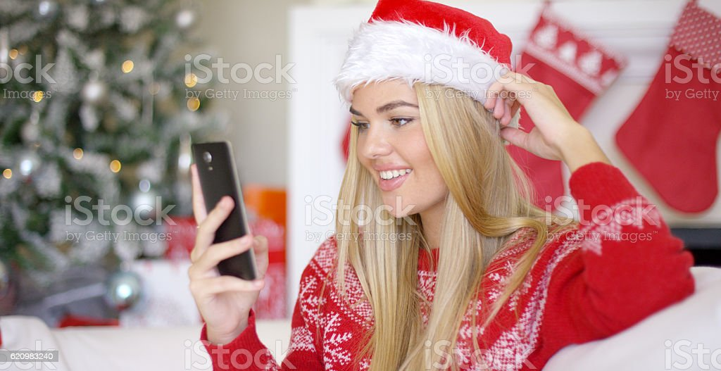 Young happy blond girl in Christmas outfit using mobile phone foto royalty-free