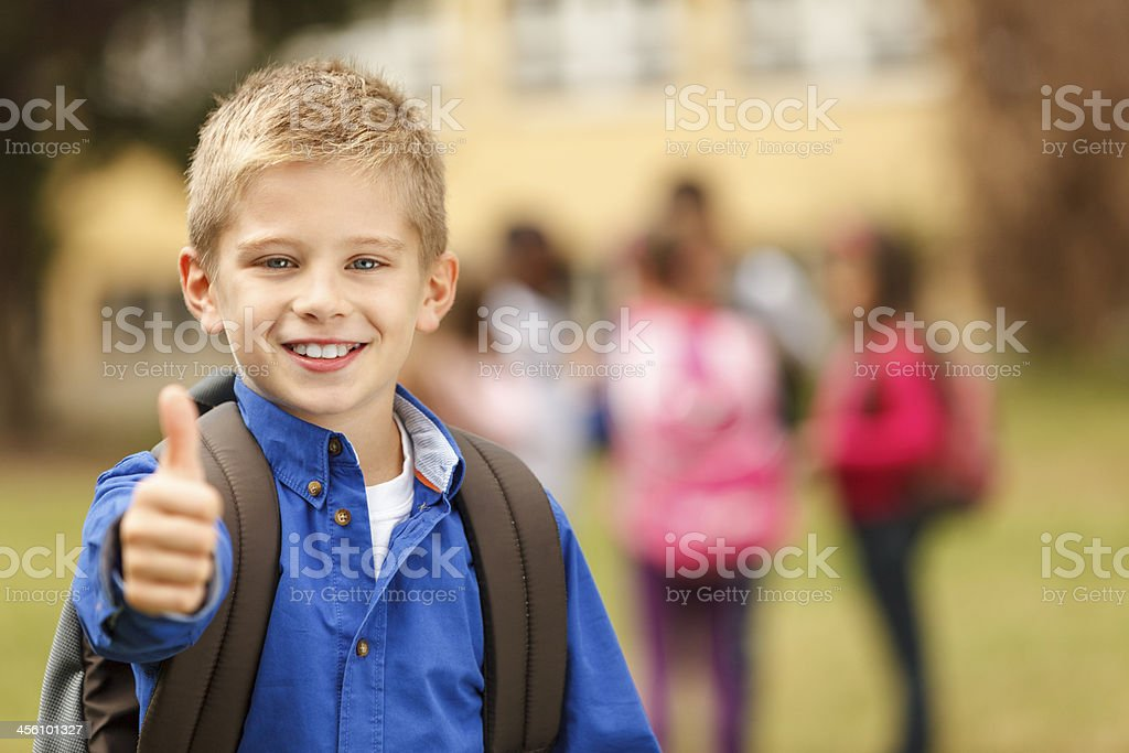 Young happy boy giving thumbs up outside school stock photo