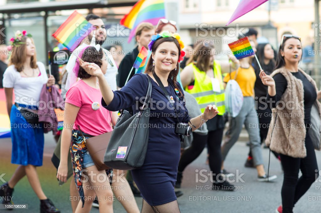 Young happy brunette waving the LGBT flag and looking into the camera stock photo