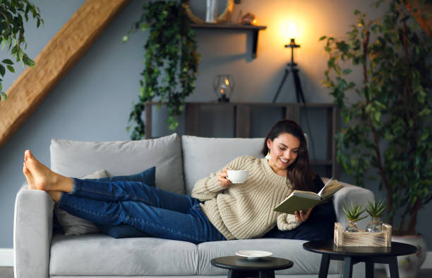 Young happy brunette woman with book wearing sweater stock photo