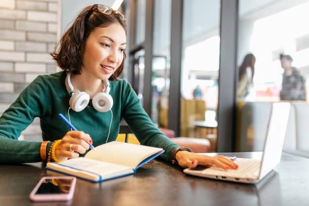Junge glückliche Geschäftsasierin, die Notizen im Notebook macht und mit Laptop-PC oder Computer arbeitet. Bildung und Arbeitskonzept. Moderne freie Berufe – Foto