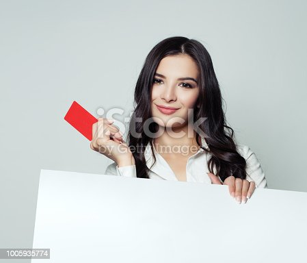 Young happy business woman showing red empty card and holding white blank banner backround. Business, advertising marketing and product placement concept