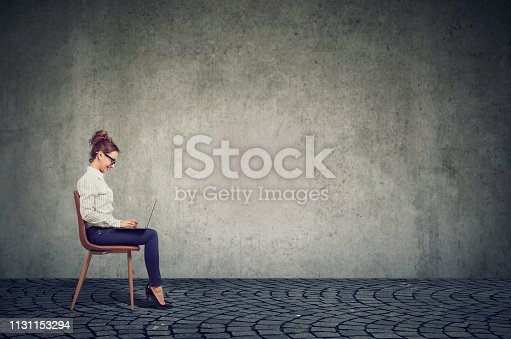 1151920695 istock photo Young happy business woman sitting on a chair using her laptop computer 1131153294