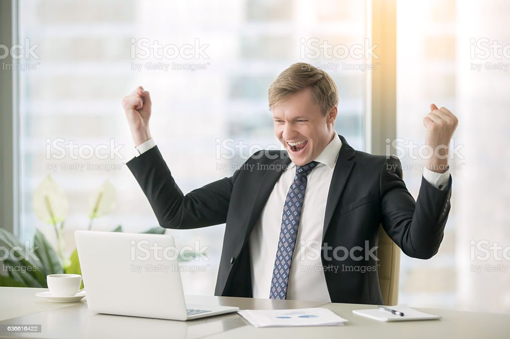 Young happy businessman at the desk stock photo