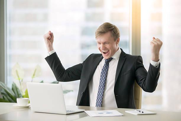 young happy businessman at the desk - die besten apps stock-fotos und bilder