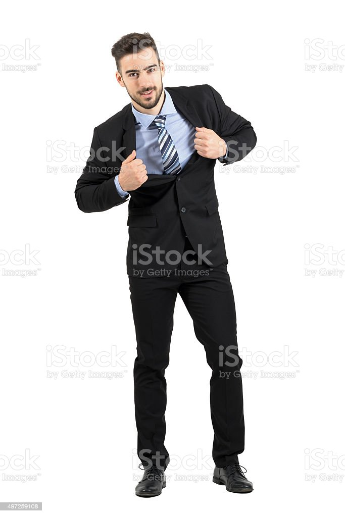 Young happy businessman pulling and stretching his suit jacket smiling stock photo
