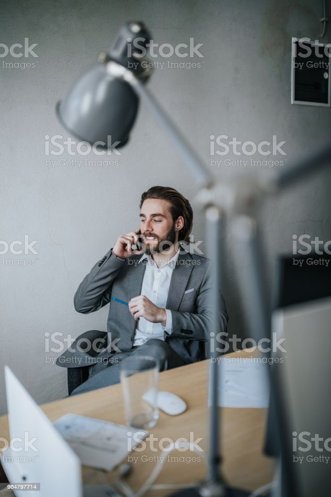 Young happy businessman talking on cell phone in the office. royalty-free stock photo