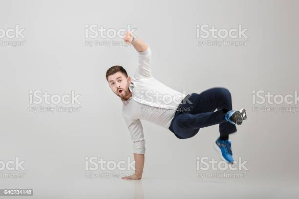 Young happy businessman with beard in shirt break dancing on picture id640234148?b=1&k=6&m=640234148&s=612x612&h=zll9u h1ok6qwxvpxaxx6p8 k5po1fro h3gbel754e=