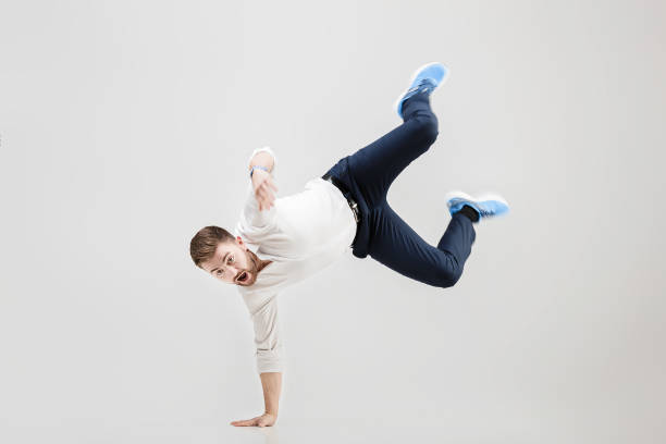 young happy businessman with beard in shirt break dancing on stock photo