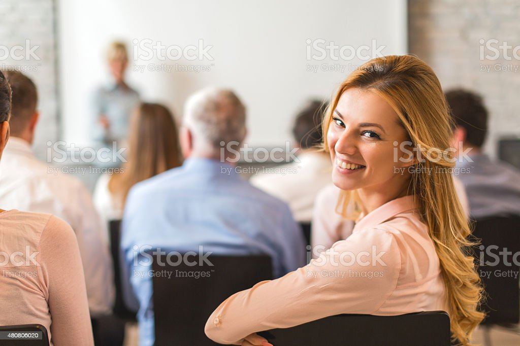 Young happy businesswoman attending a business education event. stock photo