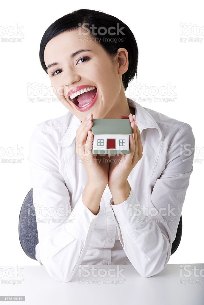 Young happy businesswoman presenting a model house royalty-free stock photo