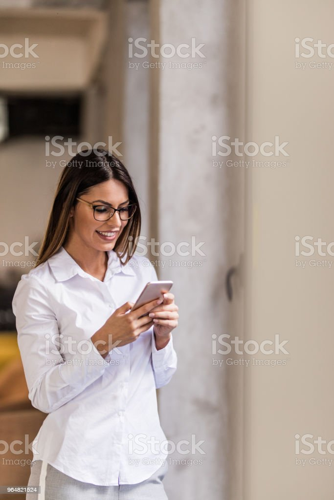 Young happy businesswoman text messaging on smart phone. royalty-free stock photo