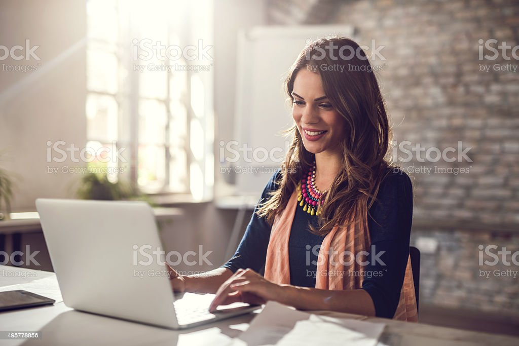 Young happy businesswoman working on laptop in the office. stock photo
