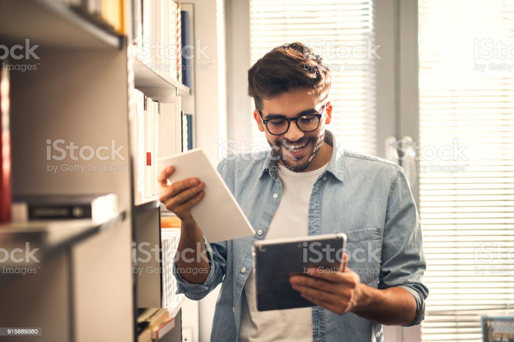 Young Happy Cheerful Hipster Student Guy Holding A Book And Tablet Next To The Bookshelf In