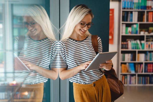 Young happy college woman studying at the library - Stock Photo Young happy college woman studying at the library - Stock Photo excitment stock pictures, royalty-free photos & images