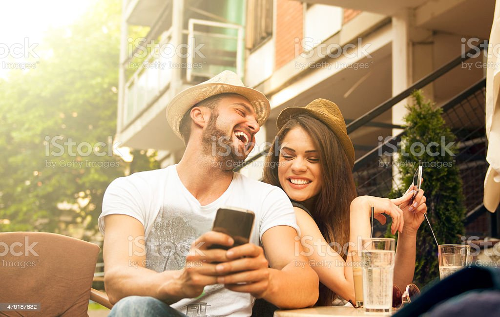 Young happy couple at cafe using smartphone stock photo