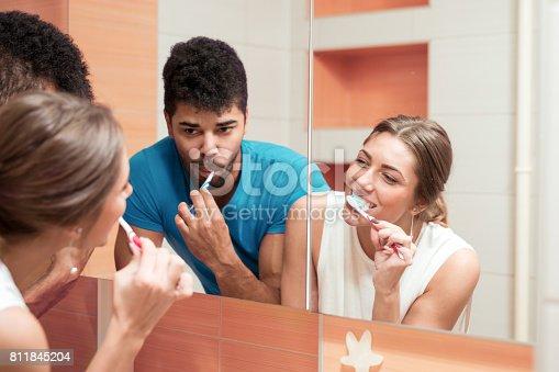 istock Young happy couple brushing teeth in the bathroom 811845204