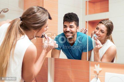 istock Young happy couple brushing teeth in the bathroom 811846432