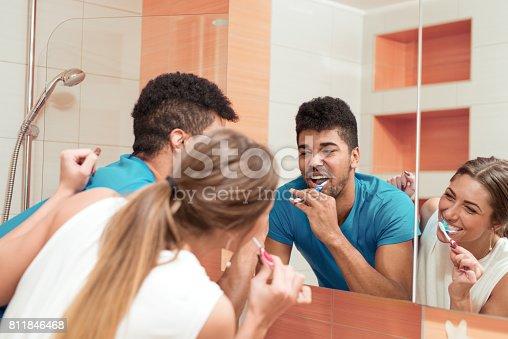 istock Young happy couple brushing teeth in the bathroom 811846468
