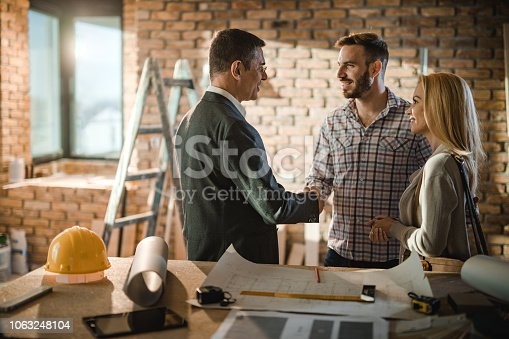 1055059750 istock photo Young happy couple came to an agreement with their investor about housing plan inside of an apartment. 1063248104