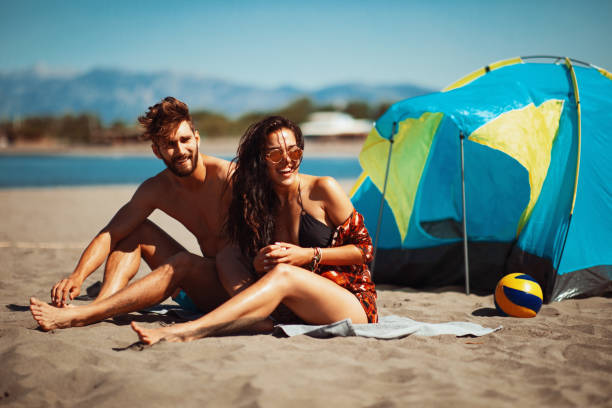 Young happy couple camping on the beach during the summer stock photo