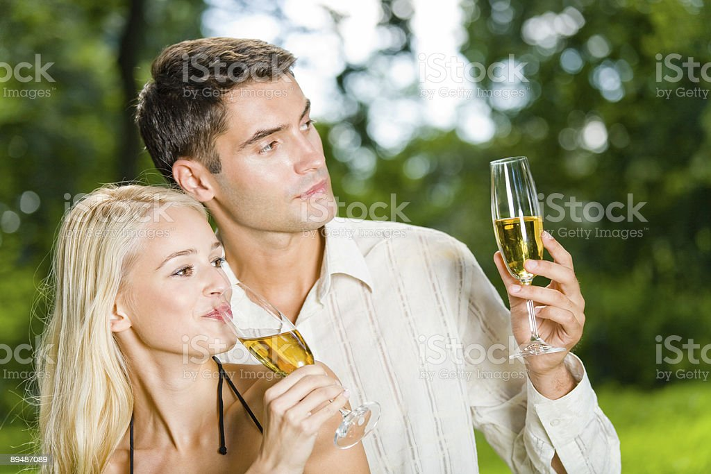 Young happy couple celebrating with champagne outdoors royalty-free stock photo