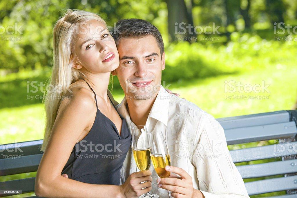 Joven pareja feliz celebrando con champán, al aire libre foto de stock libre de derechos