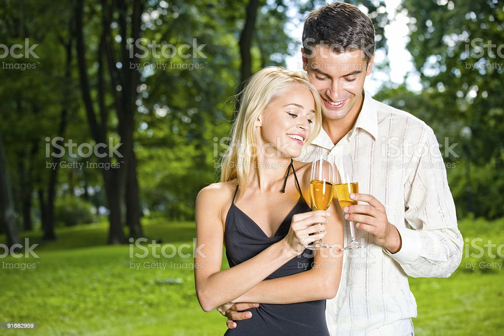 Young happy couple celebrating with champagne, outdoors royalty-free stock photo