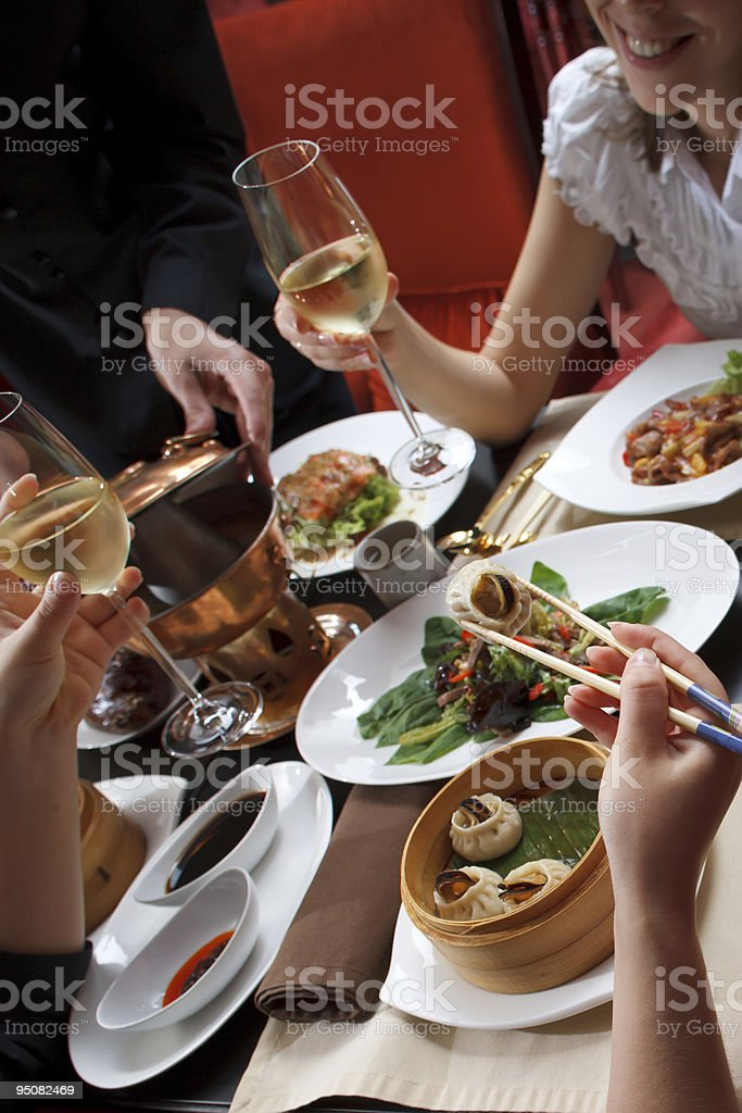 Young happy couple celebrating with white wine at chineese restaurant royalty-free stock photo