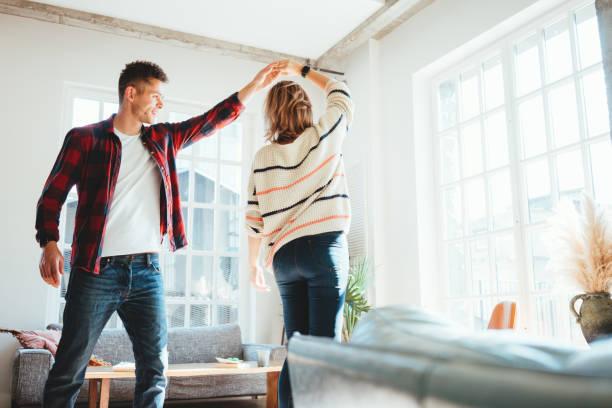 Junge glückliche Paare tanzen in der neuen Wohnung – Foto