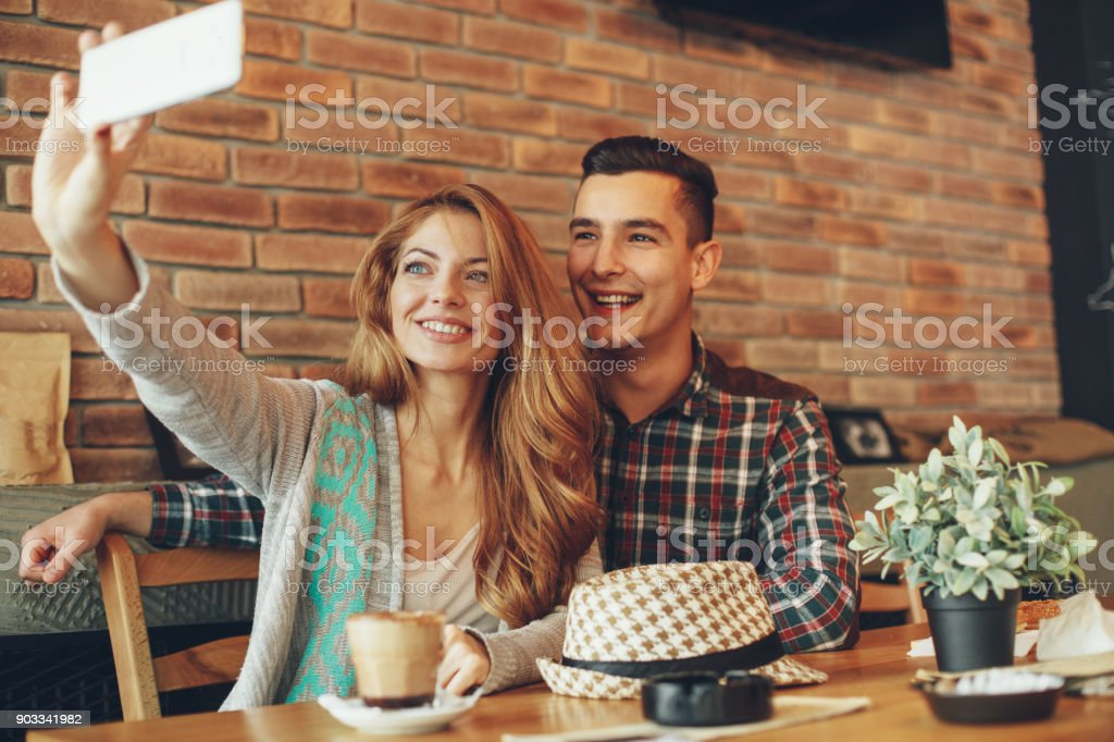 Young happy couple doing selfie in a cafe stock photo