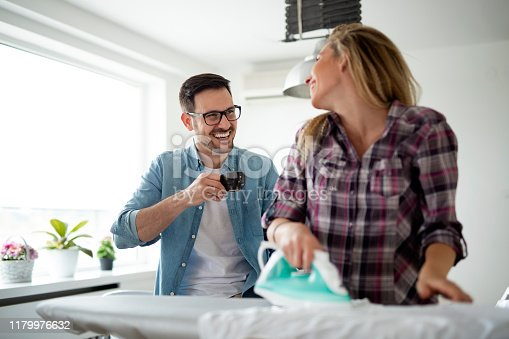 802472024istockphoto Young happy couple doing the ironing together 1179976632