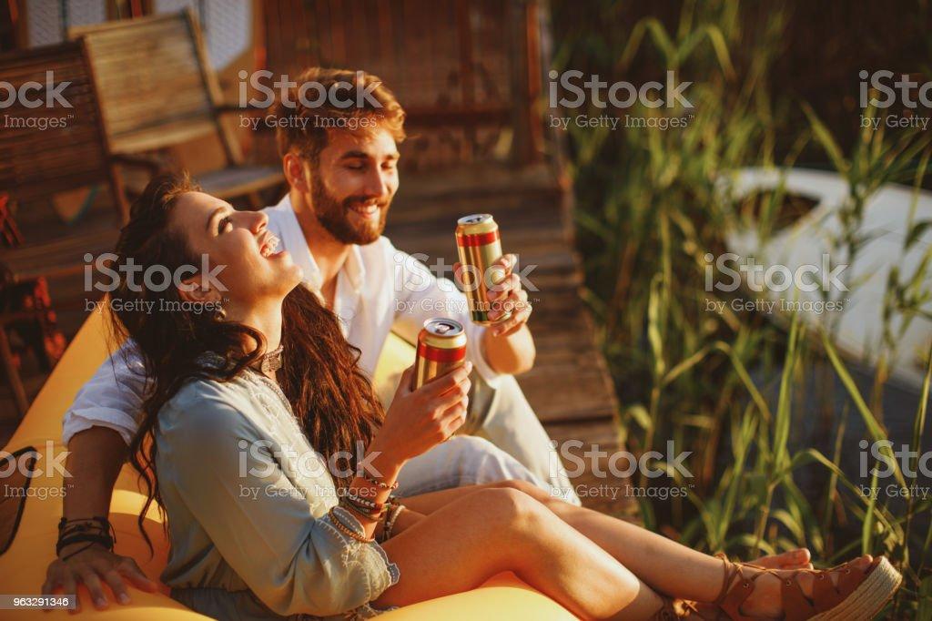 Junge Brautpaar während des Sonnenuntergangs in Bier durch den Fluss genießen. – Foto