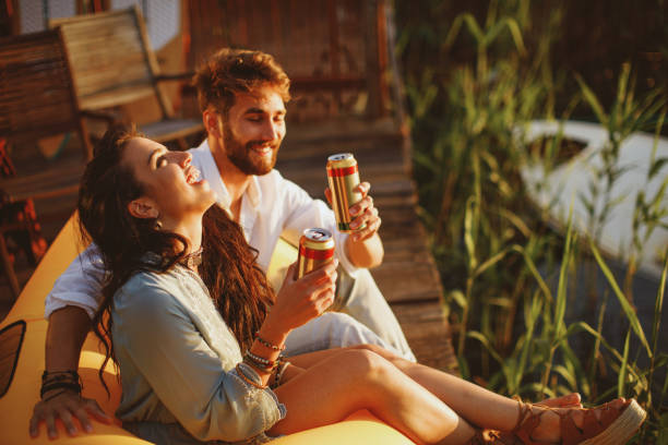 Young happy couple enjoy in beer by the river during the sunset stock photo