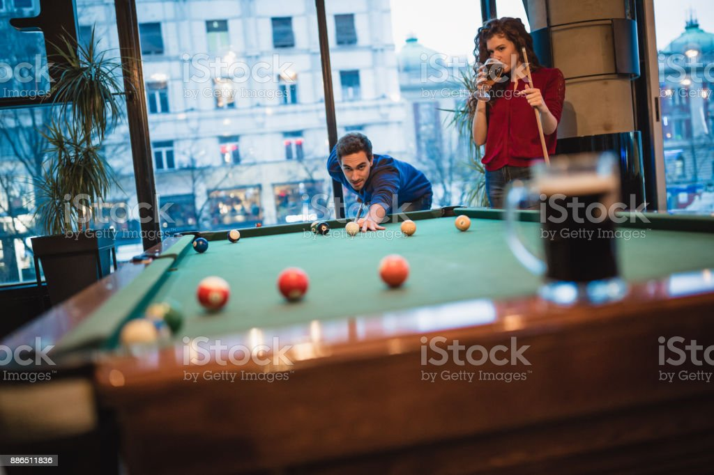 Happy man teaching his girlfriend how to play snooker. They are...