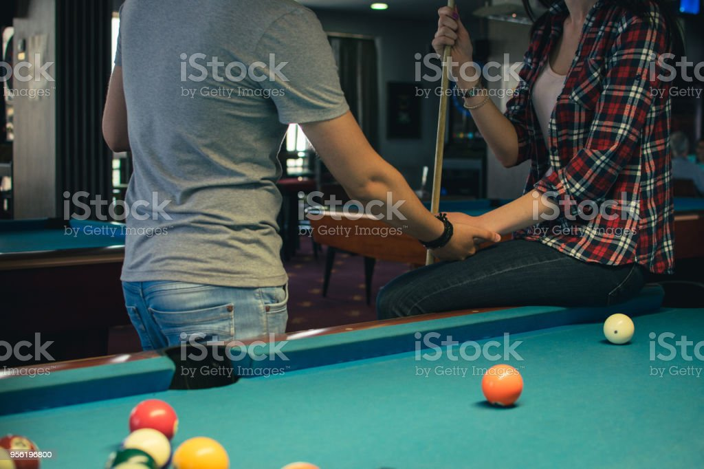Young happy couple enjoying in a billiard game together