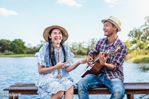 Young happy couple enjoying playing guitar and sitting at lakeside and blue sky in background