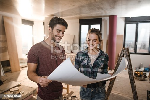 Happy couple looking at their housing project on construction site.