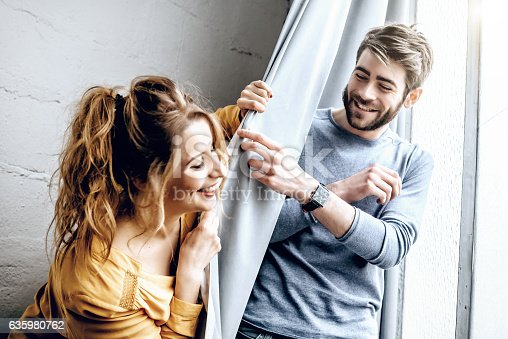 istock young happy couple fooling around with curtain in appartment 635980762