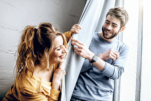 young happy couple fooling around with curtain in appartment - stupidblonde stock pictures, royalty-free photos & images