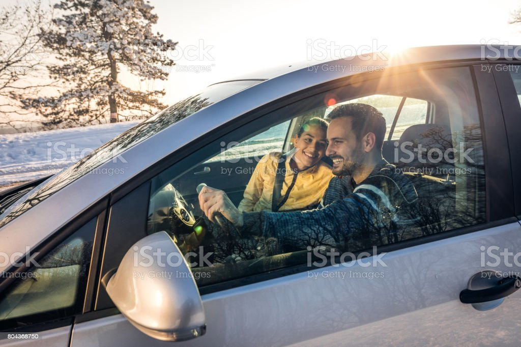 Young happy couple going on a road trip during winter day. stock photo