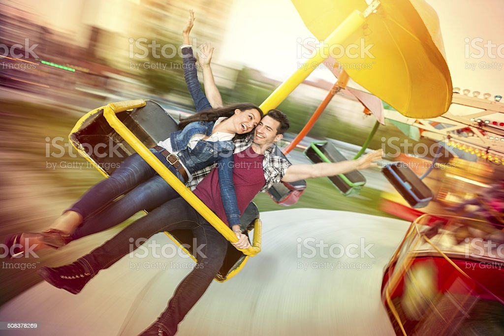 Young happy couple having fun at amusement park stock photo