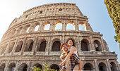 Young happy couple having fun at Colosseum, Rome. Piggyback posing for pictures.