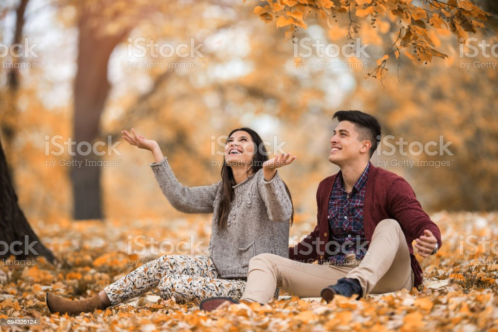 Young happy couple having fun in autumn day at the park. stock photo