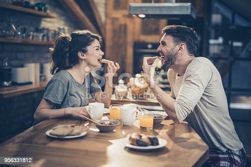 Young cheerful couple having fun while biting their sandwiches in the kitchen and looking at each other.