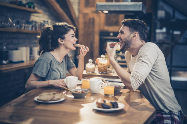 Young happy couple having fun while eating sandwiches for breakfast in the kitchen. stock photo