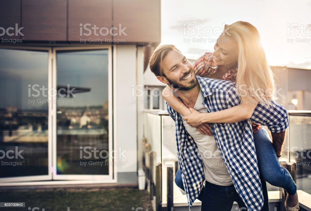 Young happy couple having fun while piggybacking on a terrace. stock photo