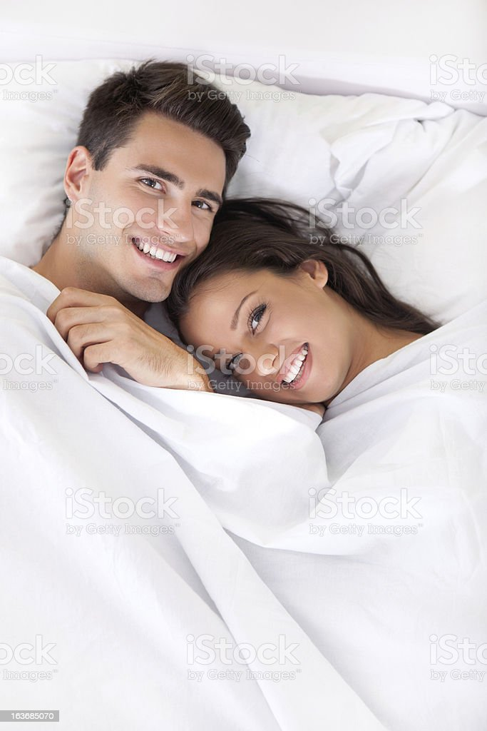 Young happy couple in bed royalty-free stock photo