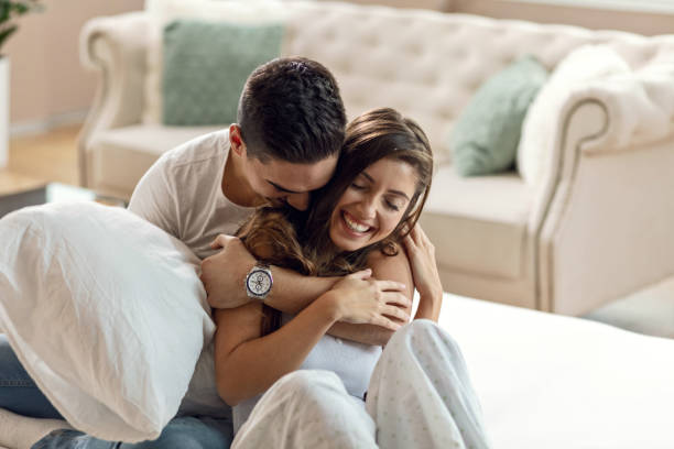 Young happy couple in love embracing in bedroom. Happy affectionate couple enjoying in their love while embracing in bedroom in the morning. romance stock pictures, royalty-free photos & images